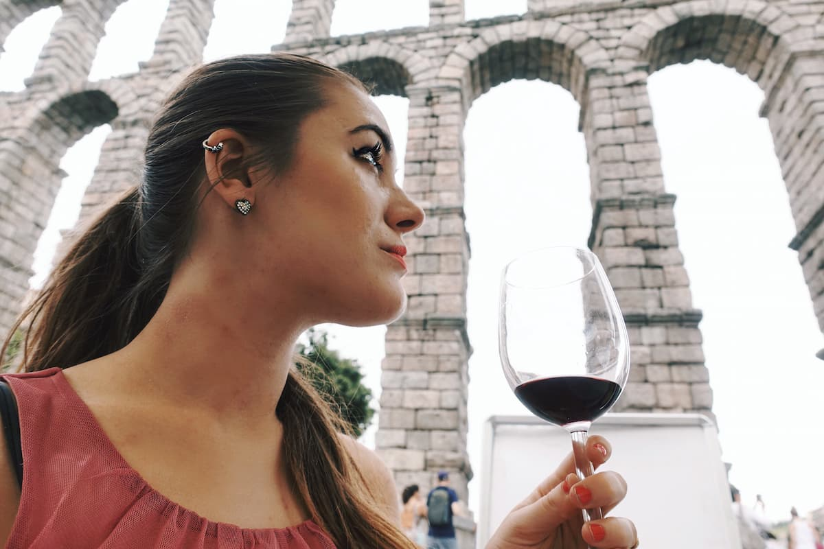 girl drinking red wine by the aqueduct of segovia